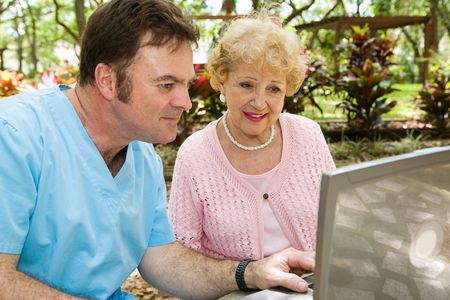 ordelijk: Senior dame ontvangen helpen op de computer van een verpleeghuis ordelijk.