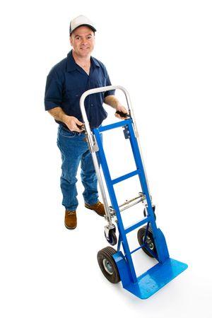 dolly: Uomo di consegna in uniforme con un camion della mano. Ente completo isolato su bianco. Archivio Fotografico