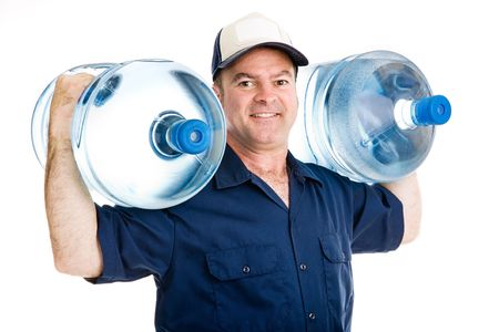 carrying: Strong water delivery man smiling as he carries two full five gallon water jugs on his shoulders.  Isolated on white.