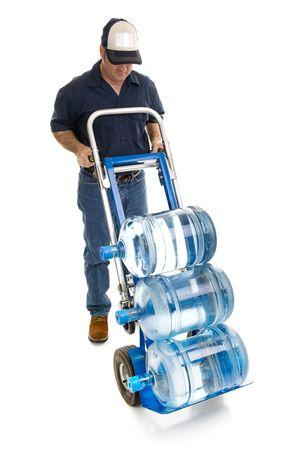 sala parto: Consegna l'uomo portare gallone cinque bottiglie di acqua su un camion a mano. Stanza per il tuo logo per il suo cappello. Corpo pieno isolati su bianco.