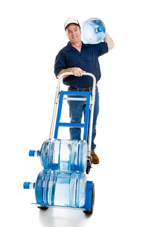 Handsome water delivery man with a five gallong jug on his shoulder and two more in the dolly.  Full body isolated on white.   photo