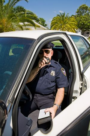 deputy sheriff: Police officer in his car calling in a license number on his radio. Stock Photo