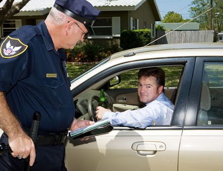traffic ticket: Police officer pulling over a drunk driver.  The driver is holding a beer and looking embarassed.   Stock Photo