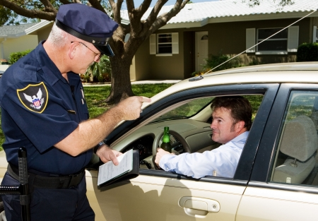 Angry police officer pulls over drunk driver, driving with an open beer. Stock Photo - 3010331