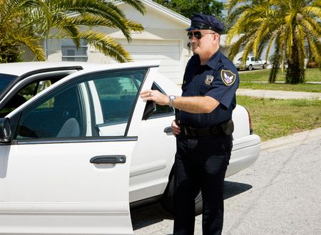Police officer getting out of his car with his citation book in his hand.   Stock Photo - 3010350
