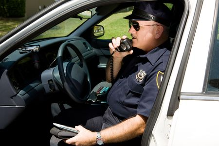 traffic ticket: Police officer in squad car, radioing in to headquarters.
