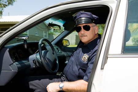 working belt: Handsome mature police officer on duty sitting in his squad car.
