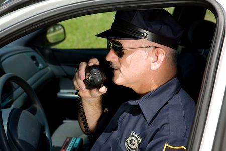 polizist: Polizist in squad Auto reden in seinem Radio. Closeup Aussicht.