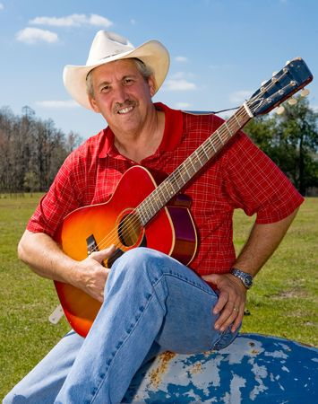 Handsome mature singing cowboy on the farm.   Stock Photo