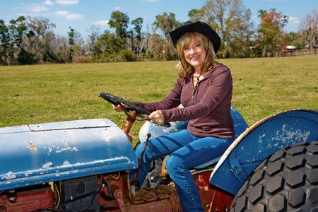 Beautiful mature woman driving a tractor on her farm.   photo