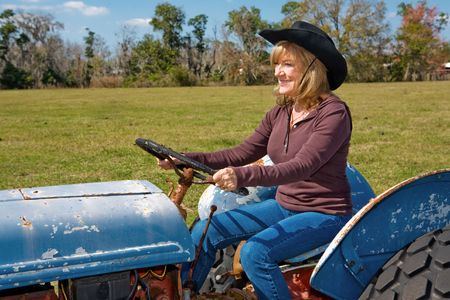 Beautiful mature woman driving a tractor on the farm. photo
