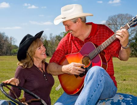 Handsome mature singing cowboy flirting with his beautiful wife.   photo