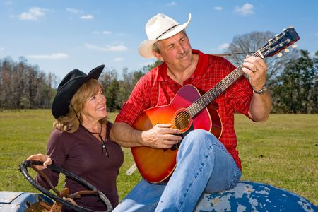 Handsome mature signing cowboy playing guitar and serenading his wife.   photo