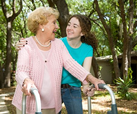 Vibrant senior lady with walker and hearing aid laughing with her teen-aged granddaughter.