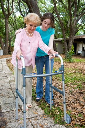 frailty: Teen girl helps her aging grandmother to walk using a walker.