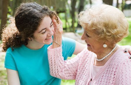 aging american: Beautiful teen girl and her loving grandmother smiling at eachother.