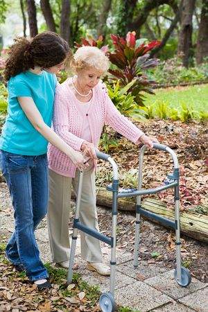 cope: Teen girl helping her grandmother cope with a walker. Stock Photo