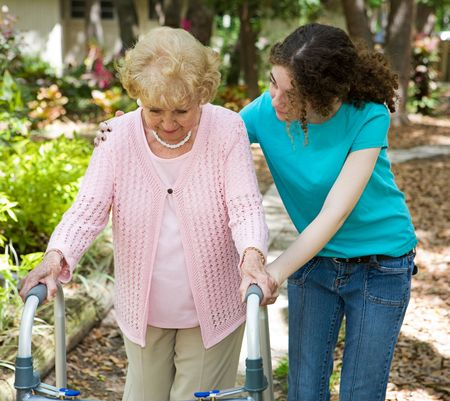 health concern: Senior woman struggles to walk with the help of a walker and her young granddaughter.