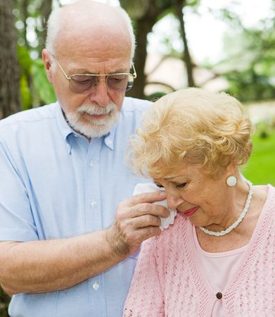 Sad senior lady cries while her husband wipes her tears.  Focus on the woman.   Stock Photo