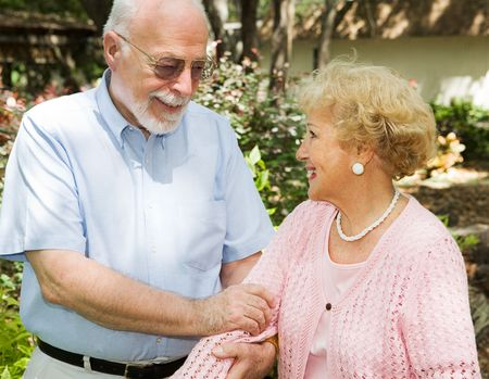 health concern: Loving senior couple enjoying a stroll outdoors. Stock Photo