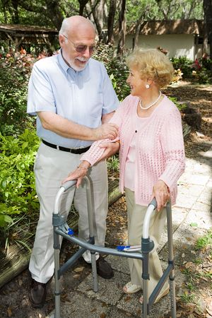 Senior couple outdoors.  She's in a walker and he's helping her.