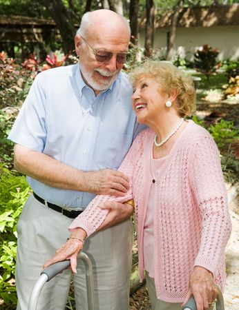 Disabled senior woman looks adoringly at her husband as he helps her walk. Stock Photo - 3051279