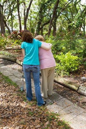 health concern: Teen girl helping senior woman walk through the park.  Vertical view with room for text. Stock Photo