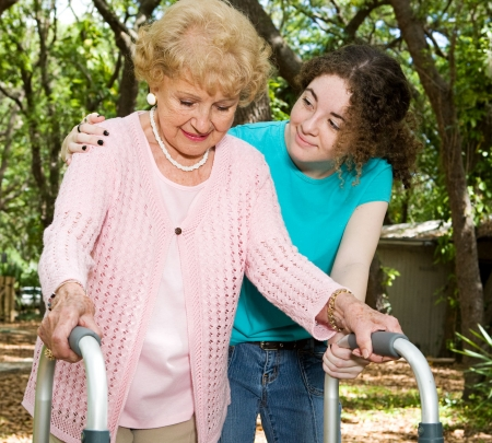 Teen girl helping a senior lady with a walker.   Stock Photo
