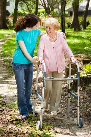 dementia: Senior woman and her teen granddaughter taking a walk in the park.