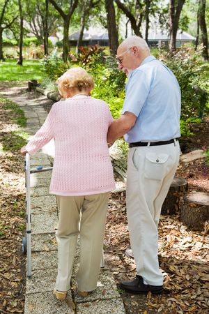 Senior couple out for a walk.  The husband is helping his wife with her walker. Stock Photo - 3051285
