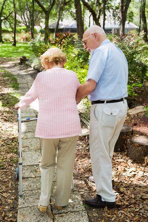 osteoporosis: Senior joven andando por el camino. El marido est� ayudando a su esposa con su andador.