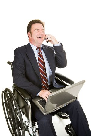 Disabled businessman in wheelchair with his computer, having a pleasant phone call.  photo
