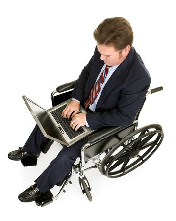 businessman working at his computer: Businessman in a wheelchair working on his laptop computer.  Full Body isolated on white. Stock Photo