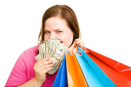 plus sized: Beautiful plus sized woman with shopping bags peeking out from behind a hand full of cash. Isolated on white.