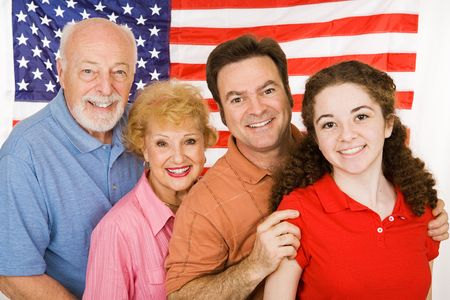 Grandparents, their adult child, and their granddaughter, posing in front of an American Flag. photo