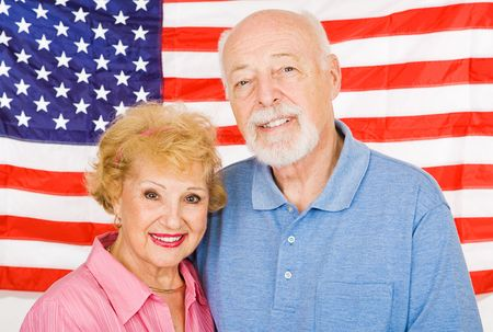 voters: Happy senior couple posing for a portrait in front of the American Flag. Stock Photo