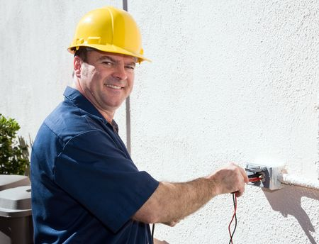 Friendly electrician testing the voltage on an outdoor receptacle.  Model is a licensed electrician and all work depicted is in compliance with federal code and safety regulations. photo