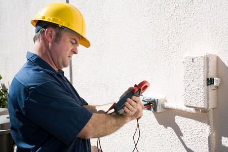 Electrician using a meter to check the voltage on an outdoor receptacle.  Model is a licensed master electrican and all work is performed according to  industry code and safety standards.   Stockfoto