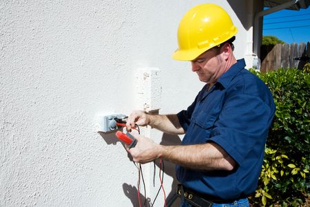 Electrician measuring voltage on an outdoor electrical receptacle.  Plenty of room for text.