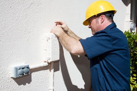 receptacle: Repairman opening an outdoor box that has been painted shut.