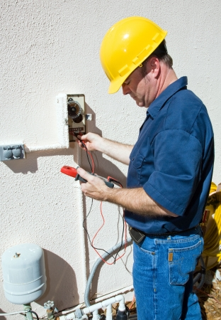 sprinklers: Electrician repairing a sprinkler pump, testing to see if its receiving power.  Focus on model.  Model is a licensed electrician, working in compliance with national code and safety regulations.   Stock Photo