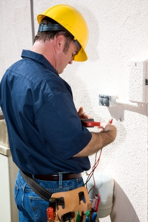 Electrician with his tool belt and voltage meter, ready to repair a faulty receptactle.  Model is an actual electrician and all work depicted is in compliance with national code and safety standards.   photo