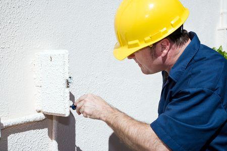 meter box: Electricista haciendo reparaciones dentro y caja el�ctrica en el exterior de una casa. Modelo es un electricista con licencia y todo el trabajo se est� realizando de acuerdo a la industria c�digo y las normas de seguridad.