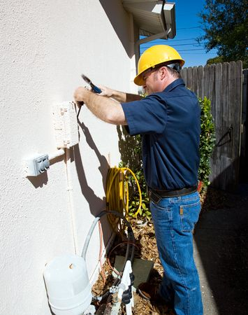 Electrican having difficulty getting into an outdoor box that has been painted shut.   photo