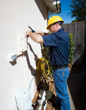 meter box: Electrican teniendo dificultades para entrar en una caja al aire libre que ha sido pintado cerrada.  Foto de archivo