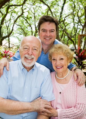 three generations of women: Adult son with his elderly parents outdoors in a natural setting.   Stock Photo