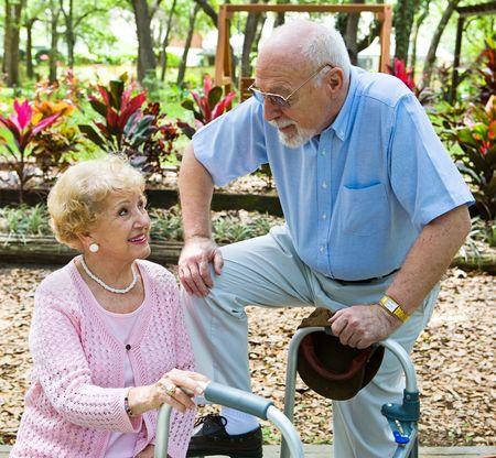 Senior man flirting with beautiful senior lady in the park.   photo