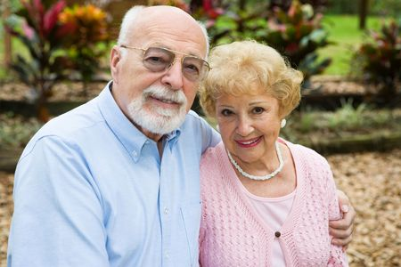 Beautiful senior couple together in their garden.  Focus on her. Stock Photo - 3105254