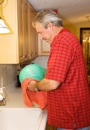 Mature man washing dishes in the kitchen.  Could be a bachelor, divorced, or helping out his wife.   photo