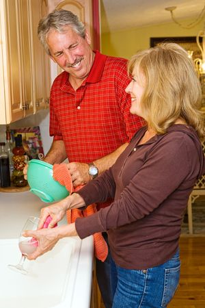 Beautiful mature couple cleaning the dishes together.   photo